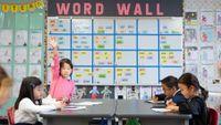 Girl raises her hand in her elementary class