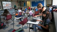 Middle school teacher helps a student at her desk in a hybrid classroom