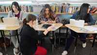 Teacher kneels down to help a student in 9th grade English class