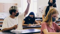 High school student raises his hand in science class