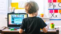 Four-year-old boy working on a virtual learning assignment on his laptop