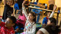A third grader raises her hand in class