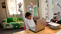 Elementary aged girl remote learning at home on computer and stretching at her desk