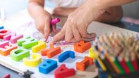 Preschooler plays with letter shapes