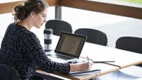 Woman takes notes while working on her laptop