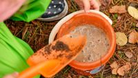 Child playing with mud in bucket