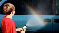 Boy sprays water from garden hose onto car and makes a rainbow.