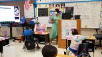 First grade teacher instructs a hybrid classroom