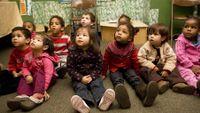 Pre-school students sitting on floor in classroom