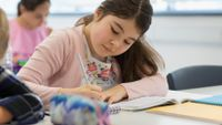 Middle school student writes in her notebook