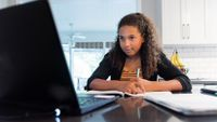 Teenage girl participates in distance learning class at home with her laptop