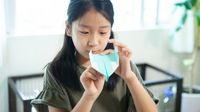 Young girl making a paper airplane at home