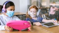 Two elementary students work together on their tablets while wearing masks in socially-distanced classroom