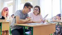Teacher works with high school student at his desk