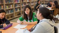 Three high school students work together in their school library