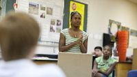 Middle school girl giving presentation in classroom at school