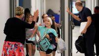 Teacher gives girl a high five in school hallway