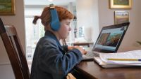 Elementary-aged girl watches National Geographic Explorer Classroom on her laptop at home