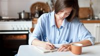 Woman writing in a notebook while sitting at her kitchen table