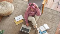 Teenage girl sitting on floor at home doing homework with laptop and books