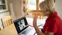 Teacher at home greeting students during online class