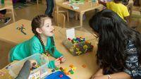Preschool student works with her teacher in class