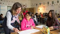 Teacher helps high school student with work in classroom