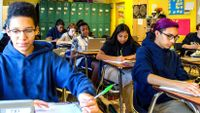 Middle school students write at their desks