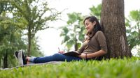 Girl writing in her notebook while sitting against a tree outside