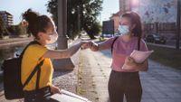 Two teenage girls greet each other with a fist bump on an urban sidewalk