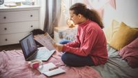 Teen girl participates in distance learning in her bedroom