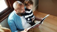 Father reads a picture book to his young son