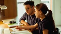 Father and daughter working on homework together at home