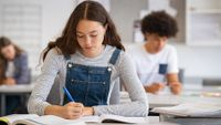 High school students writing in classroom