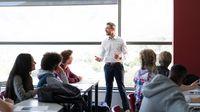 Teacher speaking to high school students in classroom.