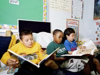 Three young boys are sitting on a couch in their classroom, reading.