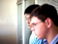 A closeup of two young, adult males looking dejected with their heads down. They're standing against a window with closed blinds.