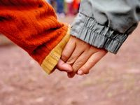 A closeup of two kids holding hands.