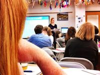"""High school students are sitting at desks in foldable chairs. A teacher is standing at the front of the class next to a large screen on the white board. The screen is displaying a presentation slide that says, """"Language Acquisition."""""""