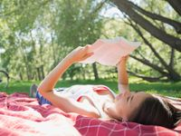 A young girl is lying on her back with a book in her hands. She's lying on a red and white checkered blanket on the grass. She's surrounding by grass, trees, and the sun.