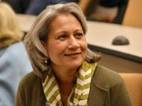 A close up of a woman from the chest up sitting in a lecture hall. She's smiling, looking off to the side, wearing a green sweater and a striped white and green scarf around her neck. She has layered, shoulder-length gray hair, peppered with brown.