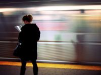 A woman in a coat is standing by a moving subway, reading a book.