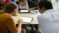 A group of four teachers are sitting at a cafeteria table, all looking at tablets.