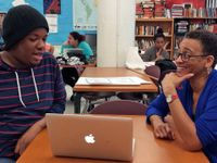 A high school student is sitting across a table from an adult in a library, and they're talking to each other. There are bookshelves against the wall behind them, as well as another table, and students sitting at desks.
