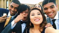 A group of five ethnic teens in formal wear are taking a selfie outside.
