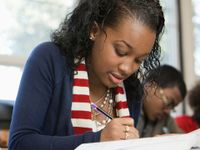 A closeup of a female high school student sitting at a desk taking a test.
