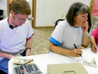 Two teachers are sitting in a classroom, calculating money.