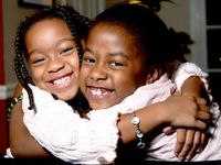Two young girls are smiling and hugging each other, looking at the camera.