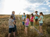Nine students are standing in a vast field with a male teacher among tall, dry grass. They're placing hand-made windmills in the field.
