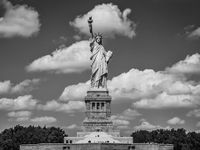 A black and white photo of the statue of liberty -- a woman in a toga, a crown, and her right arm raised up in the air, holding a torch. Behind her, the sky is filled with clouds.